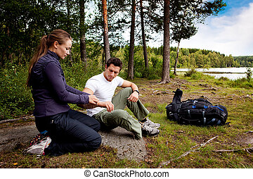 First Aid - A woman applying an arm bandage on a male camper