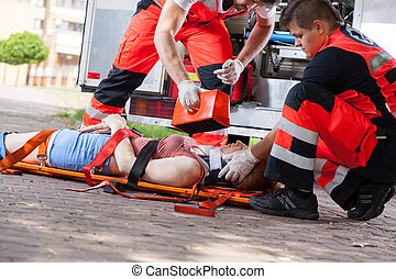 First aid after accident - Paramedics giving first aid girl...