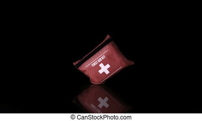 First aid kit falling on black back