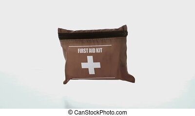 First aid kit falling on white background in slow motion