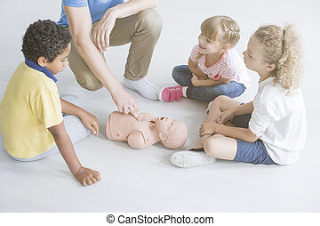 First aid on baby's manikin - Multicultural group of...