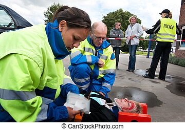 First Aid - Paramedics providing first aid to an injured...