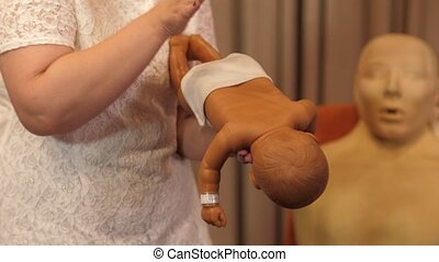 Showing on baby model how to do first aid for the baby during the first aid training