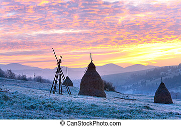 first autumn frosts on pasture with haystacks and majestic sunrise in the mountains village