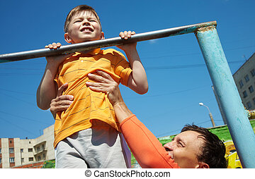First chin-up - Kid doing chin-ups, his father helping him