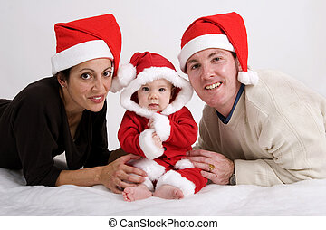 First Christmas - Young couple with baby dressed in Santa...
