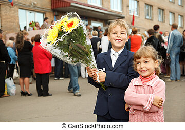 First class, brother and sister with  bouquet of flowers, standing at  entrance to school.
