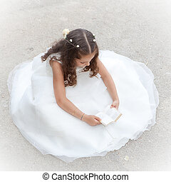 first communion or confirmation, child reading bible or...