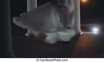 First dance of newlyweds couple in wedding ceremony. Groom turning around the bride in white dress in evening.