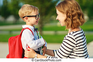first day at school. father leads a little child school boy in first grade