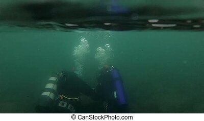first dive in cold water, diving instructor conducting a ...
