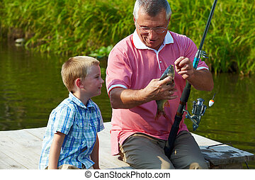 First fish - Photo of grandfather and grandson looking at...