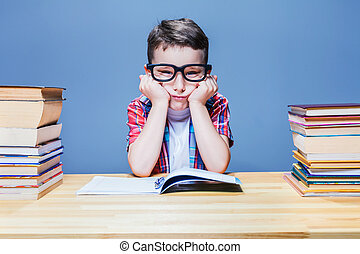 First grade child learns homework in the school library. Pupil in glasses against many books