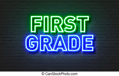 First grade neon sign on brick wall background