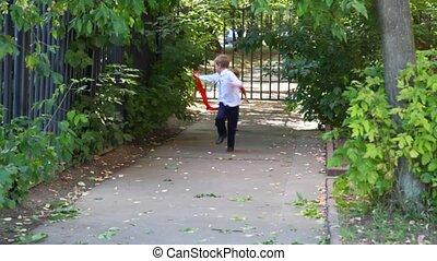 first grader boy and girl runs to camera outdoor