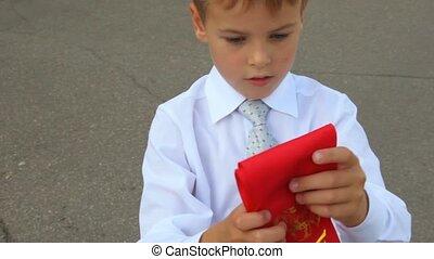 first grader boy rolls up his ribbon
