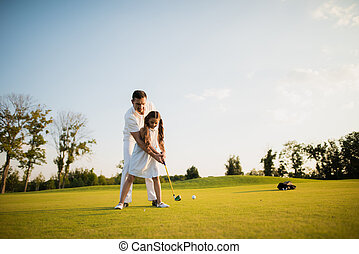 First hit. A man teaches his daughter to play golf and the girl with his help made the first golf club