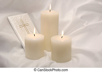 First Holy Communion lit candles and Prayer book on a white communion gown.