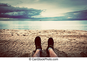 First person perspective of man legs on the autumn beach. ...