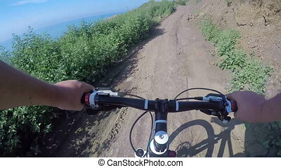 First-person POV Cyclist riding mountain bike on dirt...