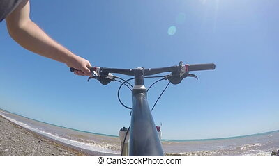 First-person POV Man traveler pushing bicycle along the wild beach
