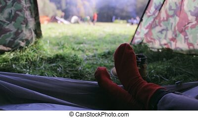 first person view from the tent in campsite on a womans legs...
