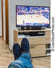 man watching a basketball game on tv