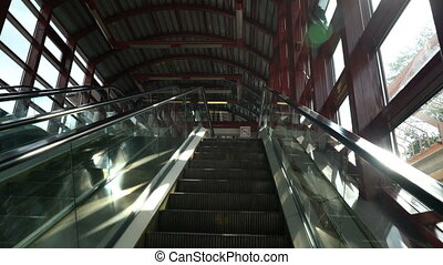 first-person view of escalator moving up on a sunny day with...