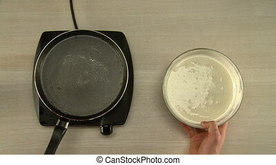 First-person view on chef cooks dough for pancakes