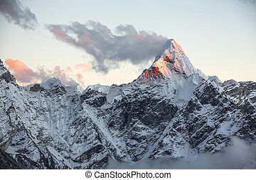 First rays of the rising sun on the top of sacred Ama Dablam peak (6814 m). Nepal, Himalayas.
