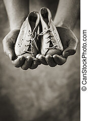 First shoes - Dirty hands holding a pair of baby shoes. Very...