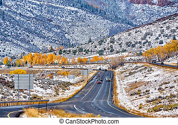 First snow and autumn trees along wet highway
