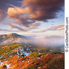 Autumn landscape in the mountains. First snow on the slopes. A small lake is covered with ice. Carpathian mountains, Ukraine, Europe