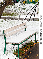 first snow on bench in city park in autumn