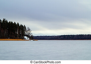 first snow on the lake in late autumn. Winter Coming Landscape