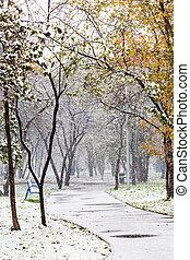 first snowfall in urban park in autumn