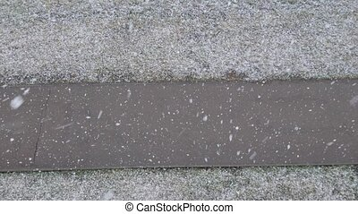 First snowfall. snow falls on the pavement, above view. slow...