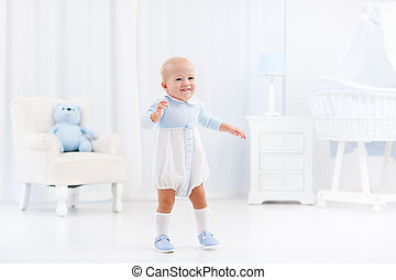 First steps of baby boy learning to walk in white sunny bedroom with bassinet, rocking chair, play mat and toy bear. Footwear for young children. Right shoes for little kids feet. Nursery interior.