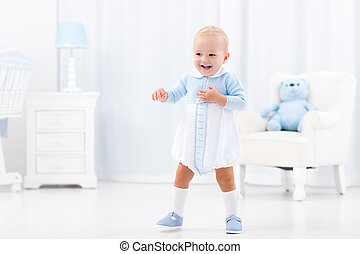 First steps of baby boy learning to walk in white sunny...