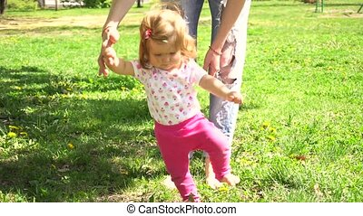 First steps of baby girl in park with mother