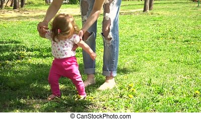 First steps of baby girl walking in park