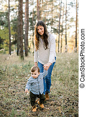 First steps of little baby boy. Outdoor shot of young charming brunette mother, walking with her cute baby toddler son in beautiful autumn pine forest at sunset