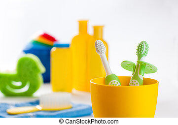 First toothbrushes in yellow glass in the bathroom