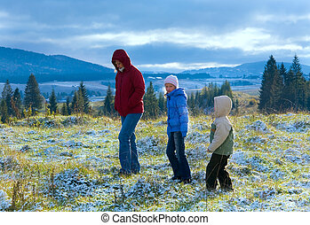 First winter snow in autumn mountain and family on walk -...