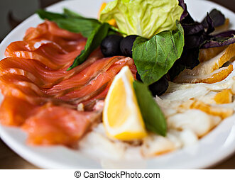 Fish appetizer with lemon and lettuce on white plate in restaurant.Healthy food.Tasty diet