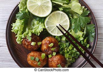 Fish balls with salad and chopsticks close-up. top view - ...