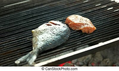 Fish being cooked on grill. Dorado and salmon meat.