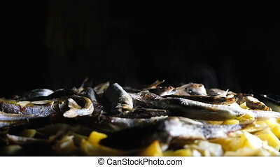 Fish capelin with potatoes on a dark background is cooked in a frying pan, slow motion