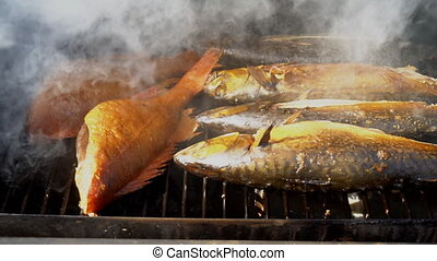 Fish cooking in smokehouse. Three sardines and sea bass.