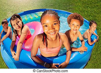 Fish eye top view of kids group in swimming pool